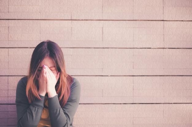Donna asiatica seduta da sola e depressa, ritratto di giovane donna stanca, depressione