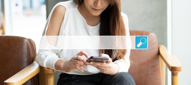 Donna asiatica seduta in una caffetteria e utilizza uno smartphone per cercare informazioni su internet, cercare la barra di navigazione internet, il concetto di ricerca navigazione dati internet information networking