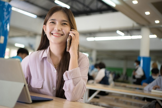 Donna asiatica seduta al lavoro in un luogo pubblico, parlando al telefono
