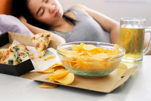 La donna asiatica dorme a letto dopo aver mangiato cibo spazzatura