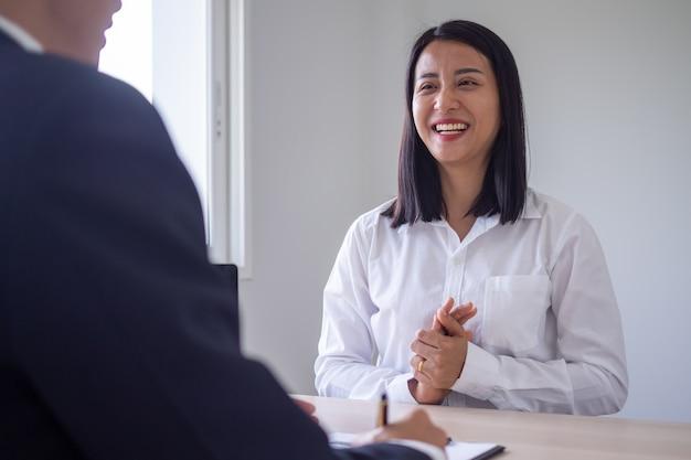 Una donna asiatica sorrise e si rilassò, intervistando un dirigente. il responsabile delle risorse umane conduce un colloquio di lavoro con i candidati in ufficio.