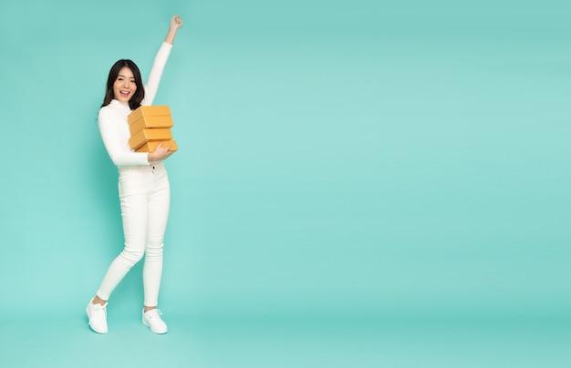Donna asiatica che sorride e che tiene la cassetta dei pacchi del pacchetto isolata su verde chiaro.