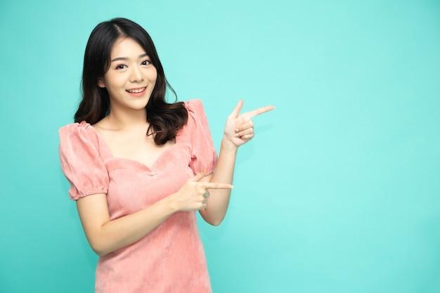 Donna asiatica sorridente e puntare il dito per svuotare lo spazio della copia isolato sul verde.