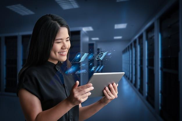 Donna asiatica che sorride con tavoletta digitale nella sala server