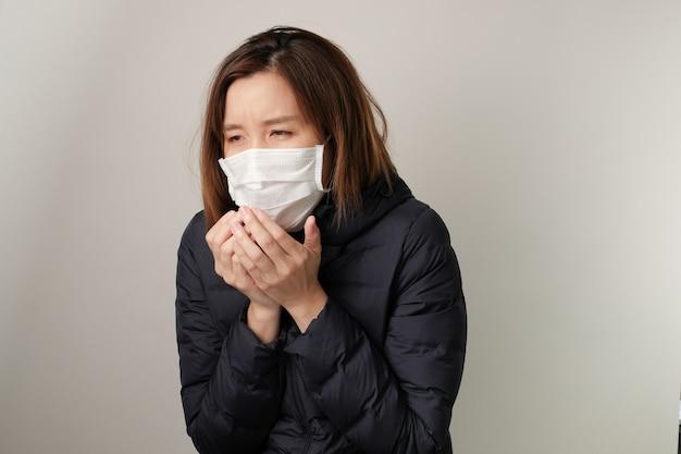 Donna asiatica che starnutisce e indossa la maschera medica per proteggere e combattere le infezioni da germi, batteri, covid19, corona, cicatrici, virus dell'influenza. concetto di malattia
