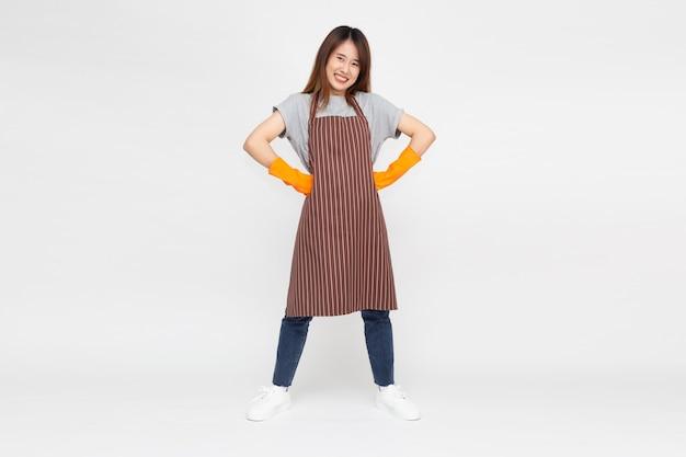 Donna asiatica in piedi e indossare guanti di gomma arancione durante la pulizia isolati su bianco.