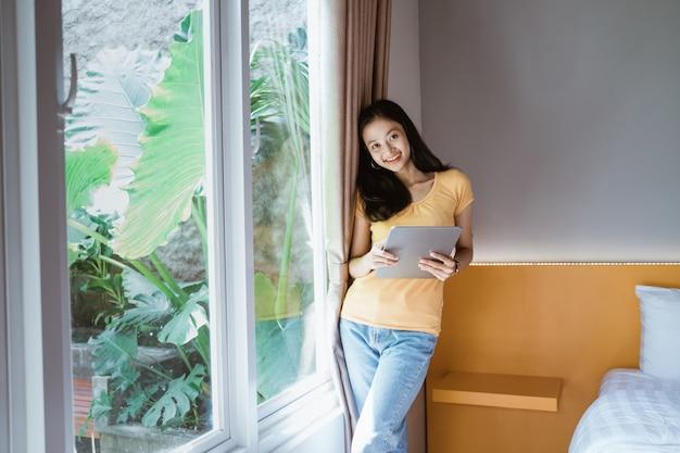 Donna asiatica in piedi accanto alla finestra con tavoletta digitale che tocca con il dito nella luce del sole del mattino