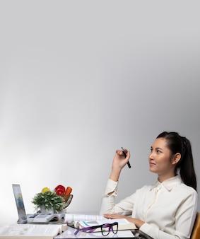 Donna asiatica studente che impara, insegna, legge libri, ricerca in taccuino