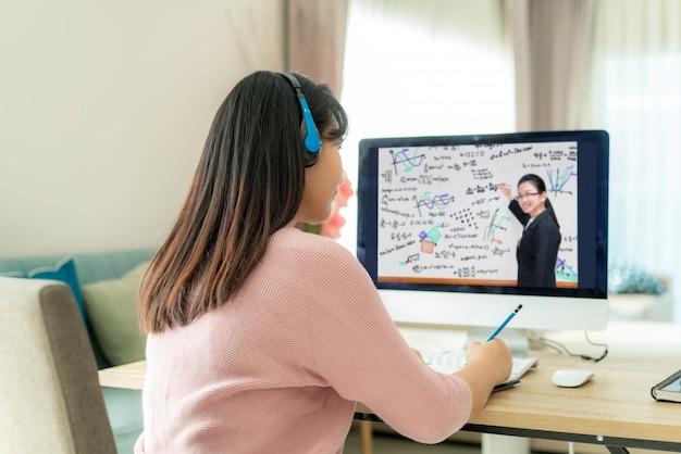 E-learning asiatico della videoconferenza della studentessa con l'insegnante sul computer in salone a casa.