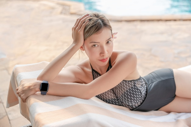 Donna asiatica che prende il sole e si rilassa sul lettino a bordo piscina
