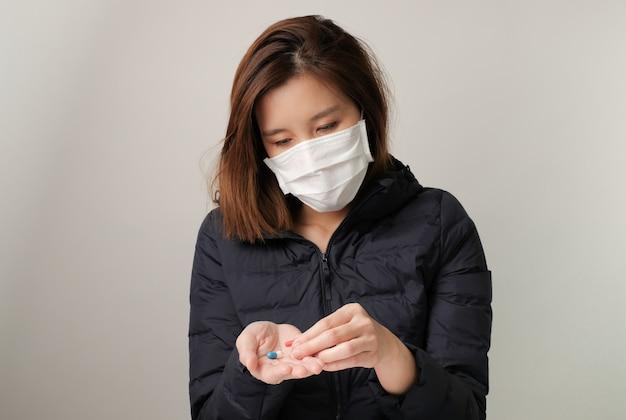 Donna asiatica prende una medicina e indossa la maschera medica per proteggere e combattere le infezioni da germi, batteri, covid19, corona, cicatrici, virus dell'influenza. concetto di malattia