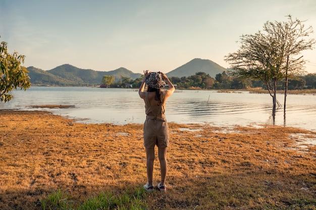 Donna asiatica che scatta una foto con lo smartphone in vista del lago di montagna al tramonto