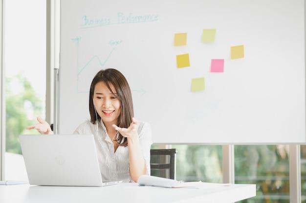 Donna asiatica parlando di business plan in videoconferenza