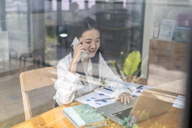 Donna asiatica che parla al telefono, è una commessa in una società di avvio, chiama i clienti per vendere prodotti e promozioni. concetto di vendita di prodotti tramite canali telefonici.