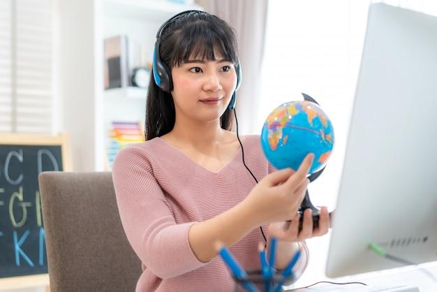 Geografia d'istruzione dell'insegnante asiatica della donna tramite e-learning di videoconferenza