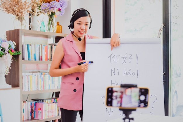 Insegnante di donna asiatica che insegna a distanza in ufficio a casa con lo smartphone di tecnologia online.