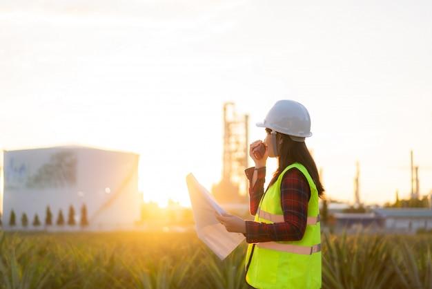 Tecnico asiatico della donna ingegnere industriale che utilizza walkie-talkie e che tiene bluprint che lavora nella raffineria di petrolio per il cantiere