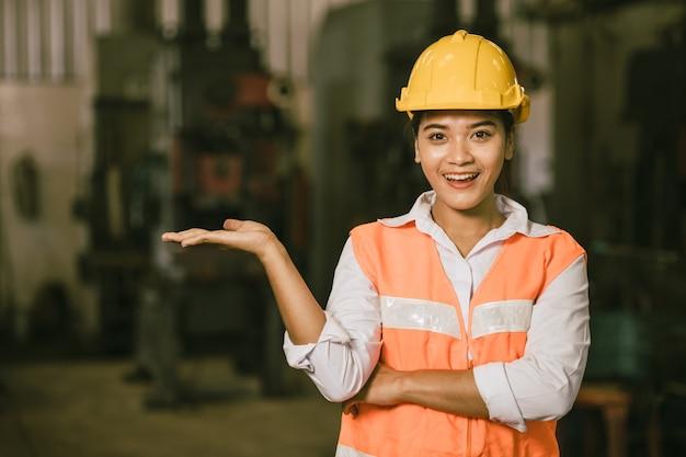 Lavoratore teenager della donna asiatica con la mano presente che mostra il fronte sorridente felice dello spazio della copia.