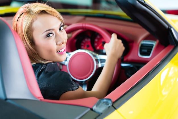 Donna asiatica che prova la nuova automobile sportiva