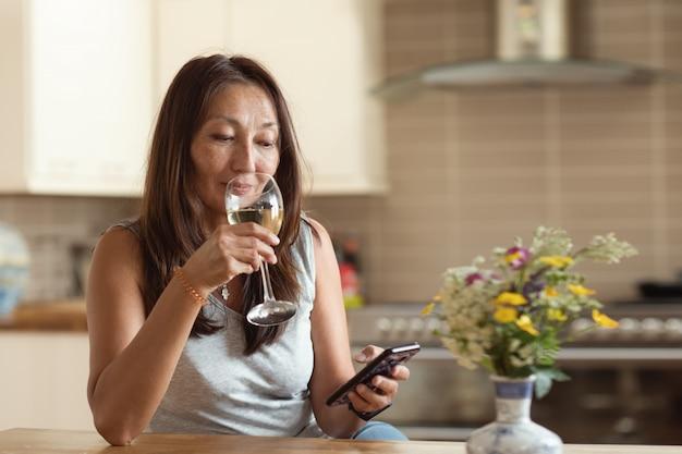 Donna asiatica che manda un sms agli amici al telefono