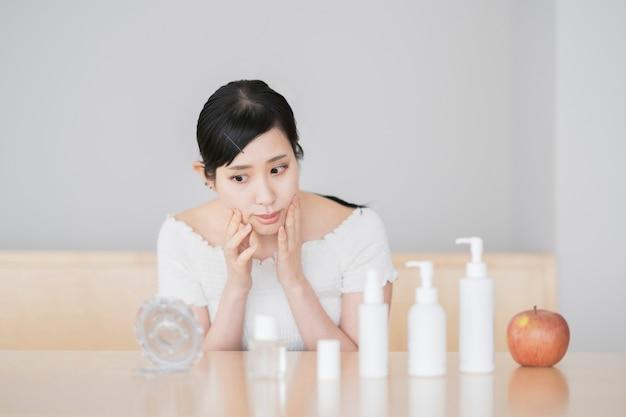 Donna asiatica che tocca e controlla la sua pelle nella stanza