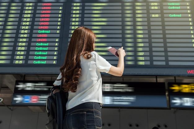 Viaggiatore asiatico della donna che tiene il passaporto e che indica al volo