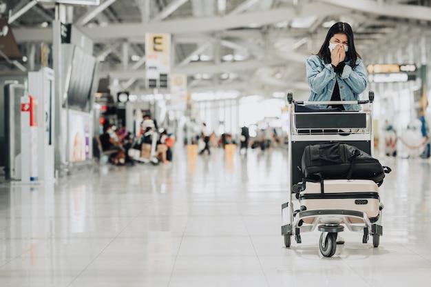 Il viaggiatore asiatico della donna che indossa la maschera protegge dal coronavirus con lo starnuto del carrello dei bagagli