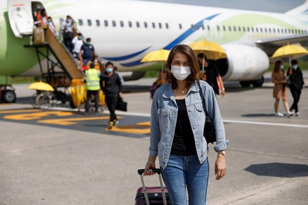 Viaggiatore della donna asiatica che indossa la borsa protettiva della tenuta della maschera di igiene che cammina nella pista dell'aeroporto. idea per un viaggio di nuovo turista normale nella pandemia di coronavirus.