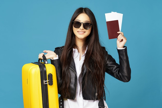 La donna asiatica viaggia con una valigia in mano, vacanze
