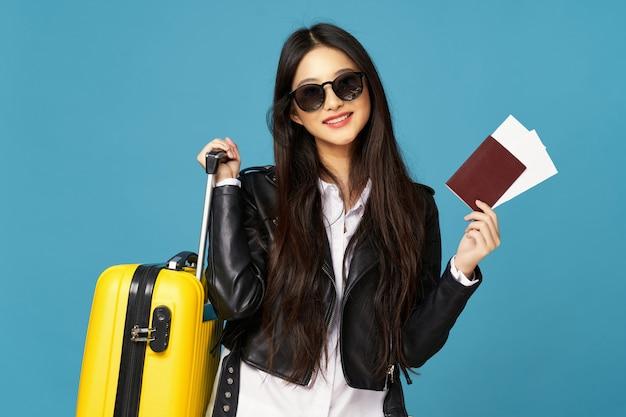 La donna asiatica viaggia con una valigia in mano, vacanze,