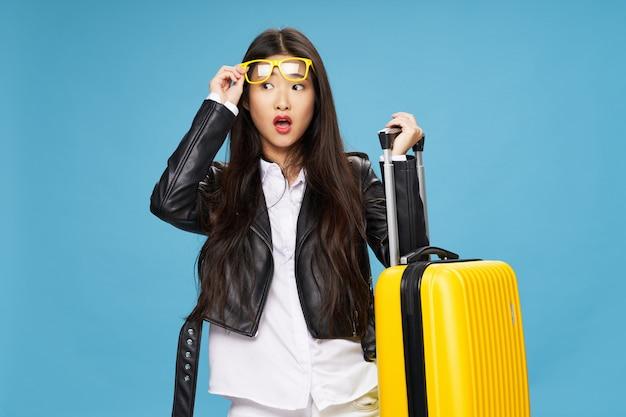 La donna asiatica viaggia con una valigia in mano.