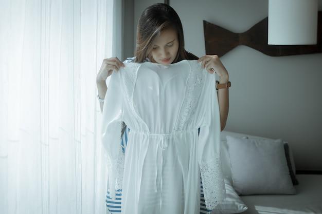 Donna asiatica che prova su una nuova veste di raso bianco a casa una ragazza ha appena comprato una nuova biancheria da notte sexy del pizzo di seta
