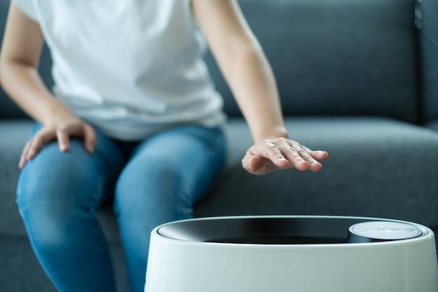 Donna asiatica che accende e usa il moderno purificatore d'aria mentre rimane in soggiorno, il purificatore d'aria è un elettrodomestico popolare: l'elettricità domestica. il purificatore d'aria può aiutare a purificare l'aria.