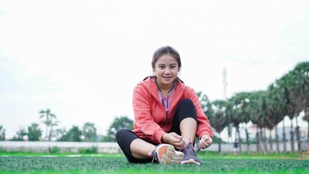 Donna asiatica che lega le scarpe da ginnastica prima di correre