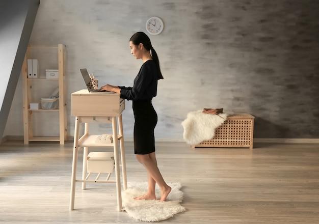 Donna asiatica che digita sul computer portatile al posto di lavoro in piedi