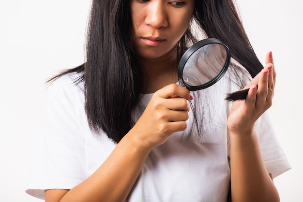 Donna asiatica infelice problema capelli deboli lei guardando i capelli distrutti con lente d'ingrandimento