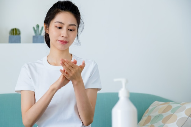 Donna asiatica con disinfettante per le mani in gel di alcol