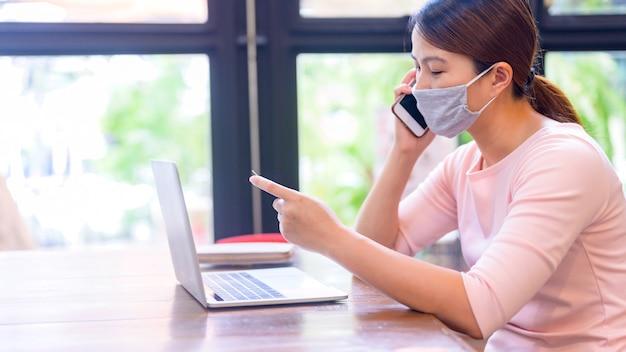 Donna asiatica che utilizza carta di credito per lo shopping online e la consegna a domicilio. nuova vita normale dopo il covid-19. resta a casa e distanziamento sociale.