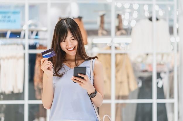Donna asiatica che usa la carta di credito con il telefono cellulare per lo shopping online nei grandi magazzini
