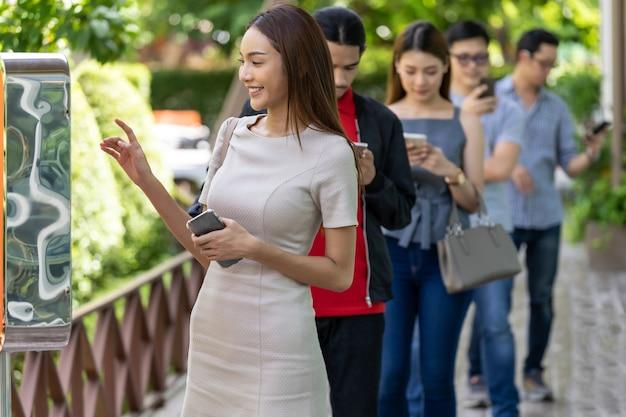 Donna asiatica che utilizza chiosco di ordinazione di cibo con coda di distanza sociale in linea prima di entrare in un ristorante fast food. tecnologia online self service nuovo normale concetto di ristorante.