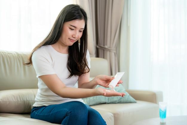 Donna asiatica che usa una lozione o idrata come mano della loro vita quotidiana affinché la pelle di protezione diventi secca e irritata dopo aver usato gel antisettico