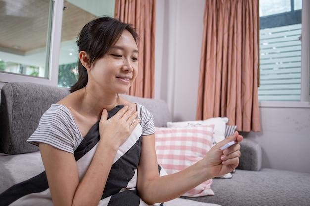 Donna asiatica che utilizza un kit di test rapido per controllare il coronavirus e il risultato è negativo. felicità dopo il test dei sintomi conosciuti. analizzare la malattia da virus con il kit di test.