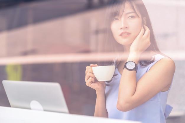 Donna asiatica che utilizza un telefono cellulare intelligente per lo shopping online nella moderna caffetteria,