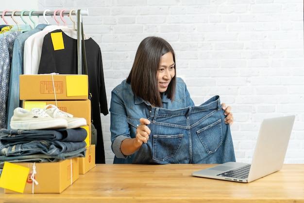 Donna asiatica che per mezzo del telefono cellulare astuto che prende i jeans online di vendita online dei pantaloni