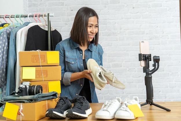 Donna asiatica che per mezzo del telefono cellulare astuto che prende le scarpe online di vendita in tensione