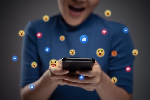 Donna asiatica utilizzando smart phone per i social media con la bolla di emoticon. isolato