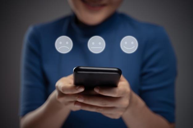 Donna asiatica utilizzando smart phone per votare con effetto ologramma emoticon. isolato