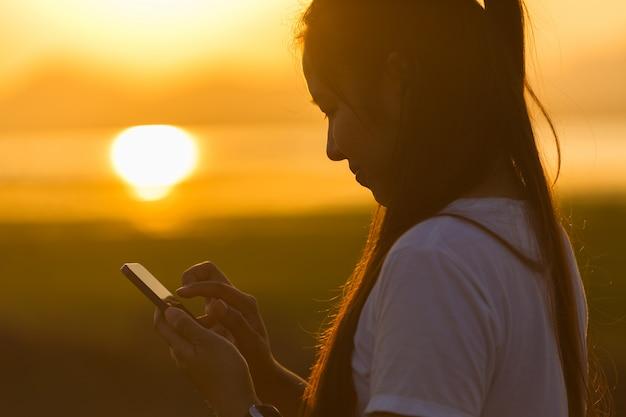 Donna asiatica che utilizza smartphone al tramonto