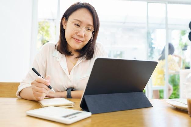 Donna asiatica utilizzando tablet, guardando lezione corso online comunicare