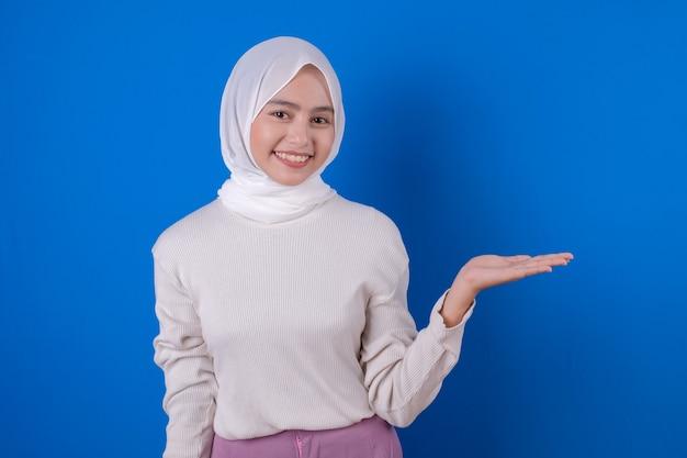 Donna asiatica che usando l'espressione di sorriso della maglietta bianca con la sua mano